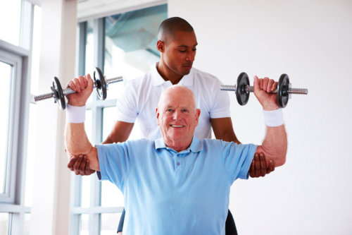 Personal trainer assisting an elderly man